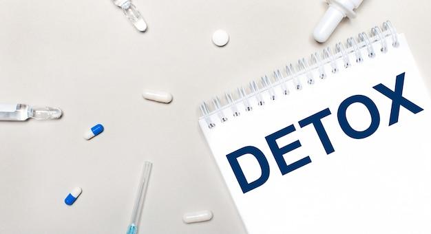 Sobre uma mesa de luz, uma seringa, um estetoscópio, frascos de remédio, uma ampola e um bloco de notas branco com o texto detox. conceito médico