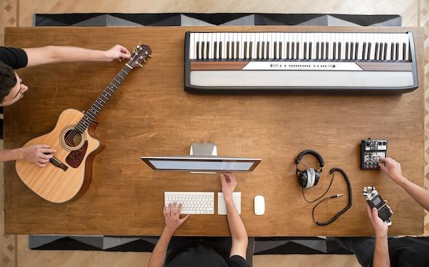 Sobre uma mesa de madeira de um estúdio de gravação, um teclado musical, um violão, uma mesa de som e um computador.