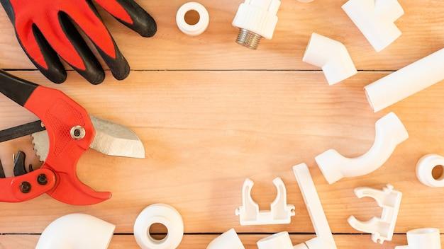 Sobre uma mesa de madeira estão os acessórios para consertar canos de água.