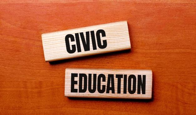 Sobre uma mesa de madeira, há dois blocos de madeira com a pergunta do texto educação cívica