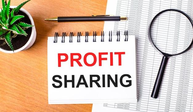 Sobre uma mesa de madeira há relatórios, um vaso de planta, uma lupa, uma caneta preta e um caderno com a inscrição partilha dos lucros. conceito de negócios