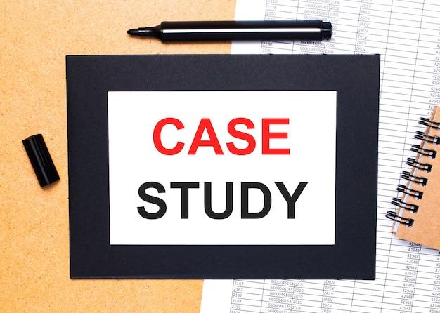 Sobre uma mesa de madeira, há um marcador preto aberto, um bloco de notas marrom e uma folha de papel em moldura preta com o texto estudo de caso. vista de cima.