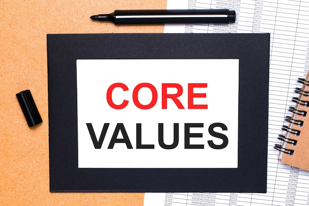 Sobre uma mesa de madeira, há um marcador preto aberto, um bloco de notas marrom e uma folha de papel em moldura preta com o texto valores centrais. vista de cima.