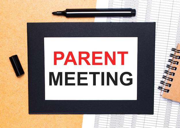 Sobre uma mesa de madeira, há um marcador preto aberto, um bloco de notas marrom e uma folha de papel em uma moldura preta com o texto reunião dos pais. vista de cima.