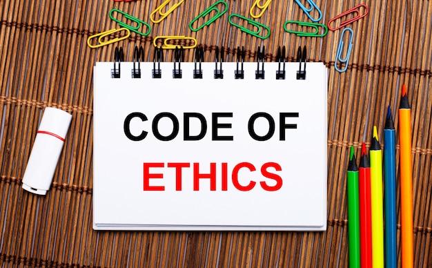 Sobre uma mesa de madeira, lápis multicoloridos, clipes de papel, um pen drive branco e um caderno com o texto código de ética