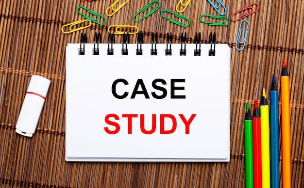 Sobre uma mesa de madeira, lápis multicoloridos, clipes de papel, um pen drive branco e um caderno com o texto estudo de caso