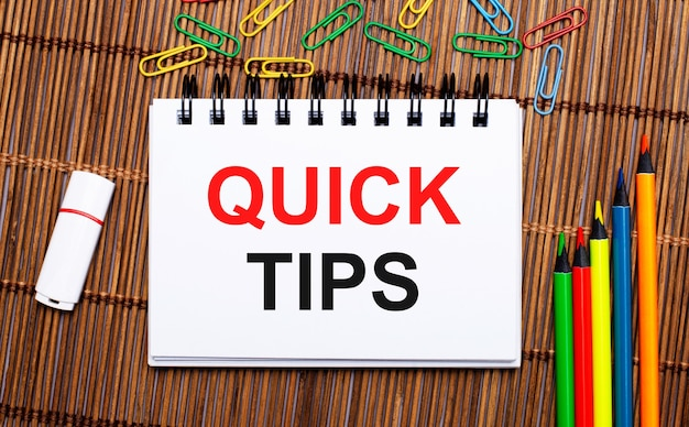 Sobre uma mesa de madeira, lápis multicoloridos, clipes de papel, uma unidade flash branca e um caderno com o texto dicas rápidas. postura plana