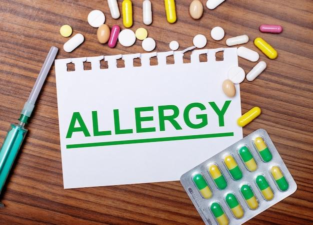 Sobre uma mesa de madeira, uma seringa, comprimidos e uma folha de papel com a inscrição alergia. conceito médico.