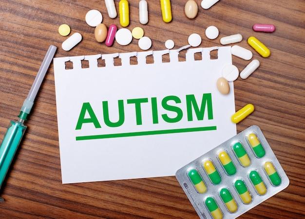 Sobre uma mesa de madeira, uma seringa, comprimidos e uma folha de papel com a inscrição autismo. conceito médico