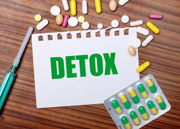 Sobre uma mesa de madeira, uma seringa, comprimidos e uma folha de papel com a inscrição detox. conceito médico