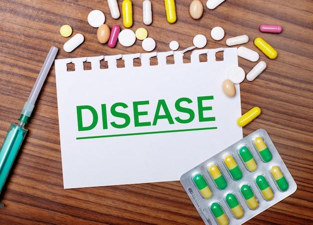 Sobre uma mesa de madeira, uma seringa, comprimidos e uma folha de papel com a inscrição doença
