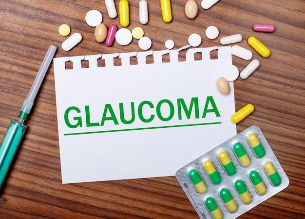 Sobre uma mesa de madeira, uma seringa, comprimidos e uma folha de papel com a inscrição glaucoma