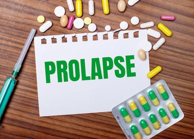 Sobre uma mesa de madeira, uma seringa, comprimidos e uma folha de papel com a inscrição prolapse. conceito médico