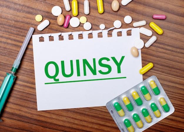 Sobre uma mesa de madeira, uma seringa, comprimidos e uma folha de papel com a inscrição quinsy. conceito médico