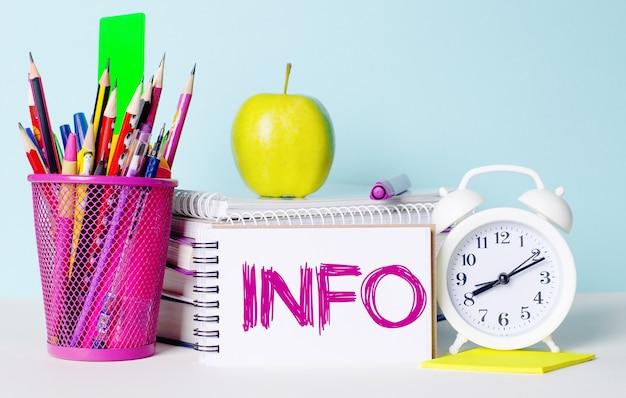 Sobre uma mesa iluminada há livros, artigos de papelaria, um despertador branco, uma maçã. ao lado está um bloco de notas com o texto info. conceito educacional.