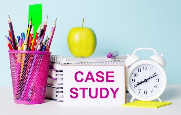 Sobre uma mesa iluminada há livros, artigos de papelaria, um despertador branco, uma maçã. ao lado está um caderno com o texto estudo de caso. conceito educacional.