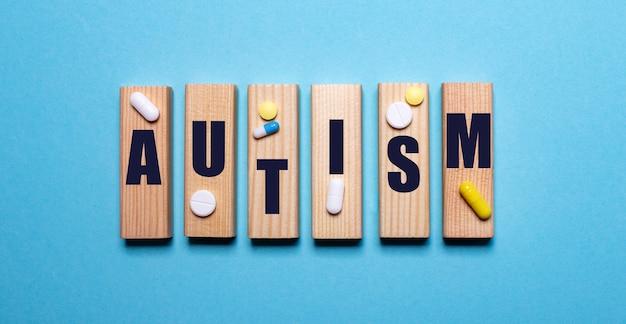 Sobre uma superfície azul, blocos de madeira com a palavra autismo e comprimidos. conceito médico