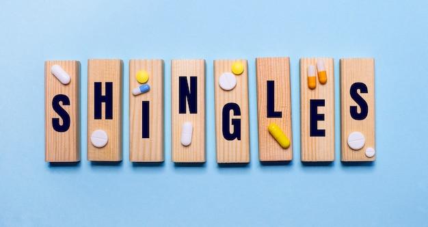 Sobre uma superfície azul, blocos de madeira com a palavra shingles e comprimidos. conceito médico