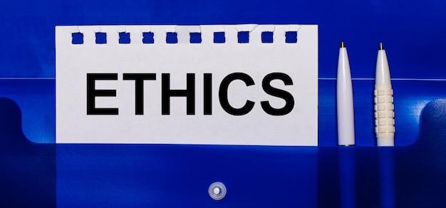 Sobre uma superfície azul, canetas brancas e uma folha de papel com o texto ética
