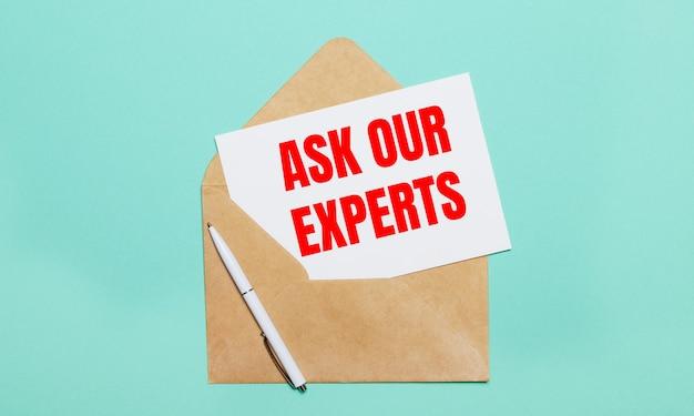 Sobre uma superfície azul clara está um envelope aberto, uma caneta branca e uma folha de papel branca com o texto pergunte ao nosso especialista