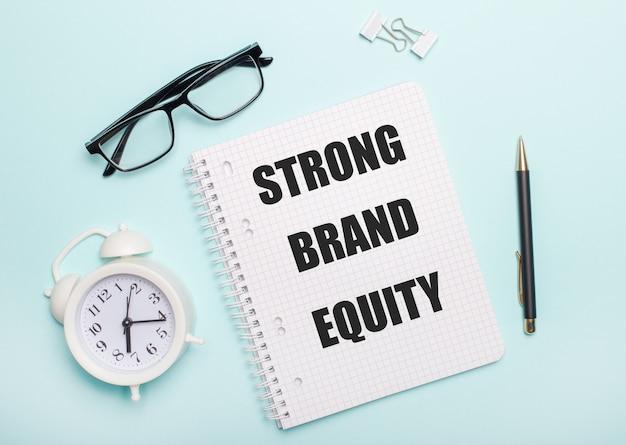 Sobre uma superfície azul clara estão óculos pretos e uma caneta, um despertador branco, clipes de papel brancos e um caderno com as palavras strong brand equity