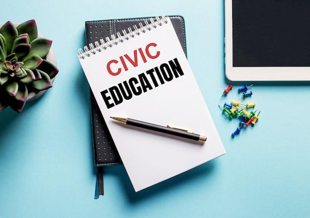 Sobre uma superfície azul clara, há um vaso de planta, um comprimido e um semanário com o texto educação cívica
