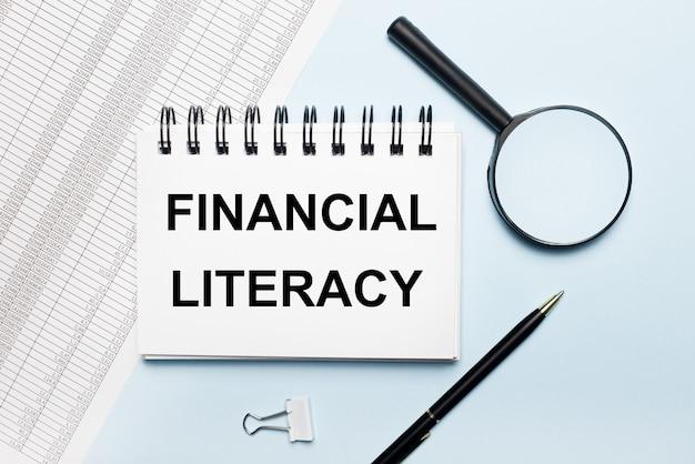 Sobre uma superfície azul clara, relatórios, uma lupa, uma caneta e um caderno com o texto alfabetização financeira
