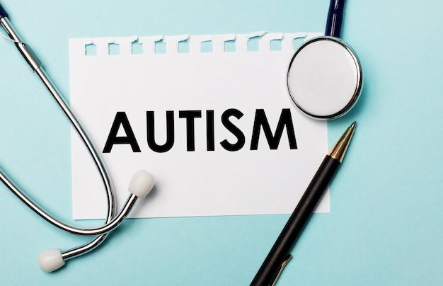 Sobre uma superfície azul clara, um estetoscópio, uma caneta e uma folha de papel com a inscrição autismo. conceito médico