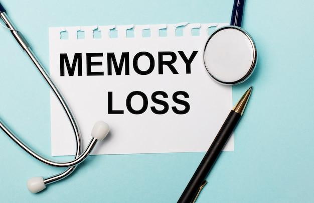 Sobre uma superfície azul clara, um estetoscópio, uma caneta e uma folha de papel com a inscrição perda de memória