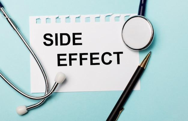 Sobre uma superfície azul clara, um estetoscópio, uma caneta e uma folha de papel com a inscrição side effect. conceito médico