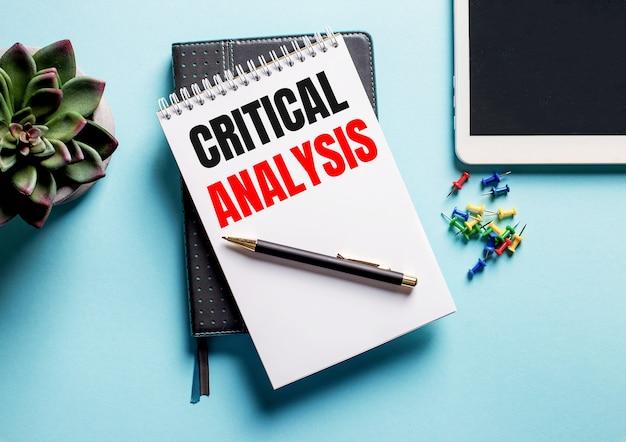 Sobre uma superfície azul claro, há um vaso de planta, um tablete e um semanário com o texto análise crítica