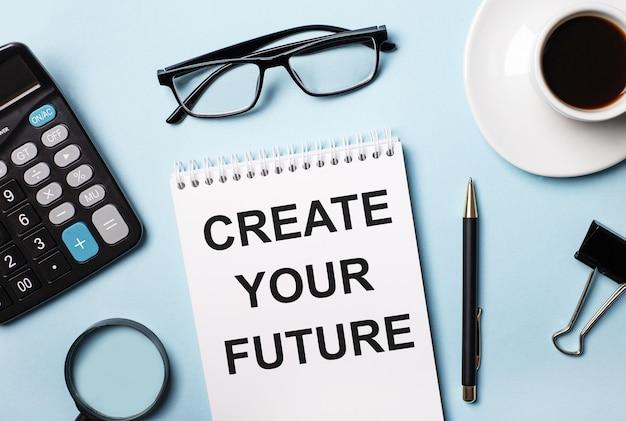 Sobre uma superfície azul, óculos, calculadora, café, lupa, caneta e caderno com o texto crie seu futuro
