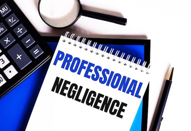 Sobre uma superfície azul, próximo à calculadora, lupa e caneta, caderno com a inscrição negligência profissional