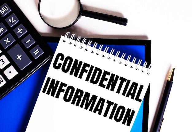 Sobre uma superfície azul, próximo à calculadora, lupa e caneta, um caderno com a inscrição informações conidenciais
