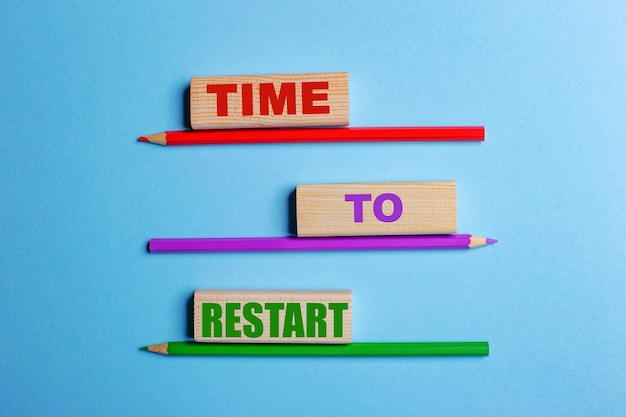 Sobre uma superfície azul, três lápis de cor, três blocos de madeira com o texto hora de reiniciar