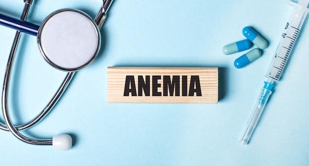 Sobre uma superfície azul, um estetoscópio, uma seringa e comprimidos e um bloco de madeira com a palavra anemia. conceito médico