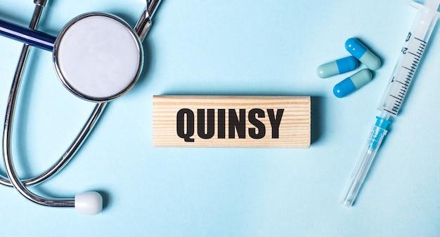 Sobre uma superfície azul, um estetoscópio, uma seringa e pílulas e um bloco de madeira com a palavra quinsy. conceito médico.
