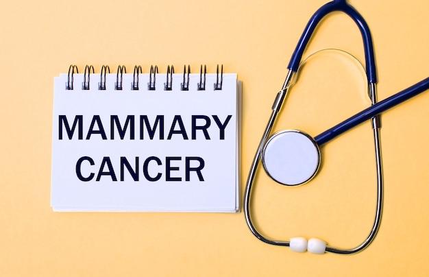 Sobre uma superfície bege, um estetoscópio e um bloco de notas branco com a inscrição câncer de mamária