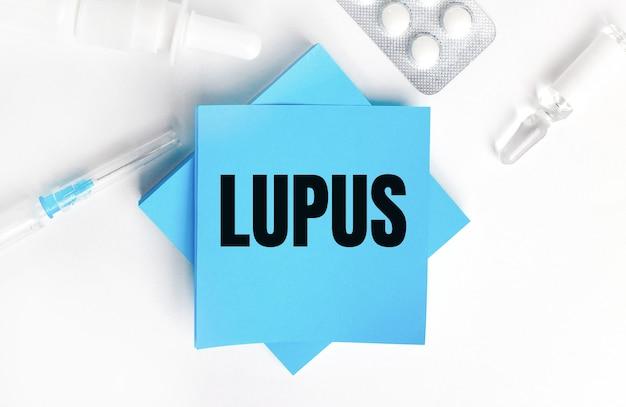 Sobre uma superfície branca, uma seringa, ampola, pílulas, um frasco de remédio e adesivos azuis claros com a inscrição lúpus. conceito médico