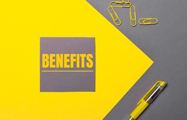 Sobre uma superfície cinza e amarela, um adesivo cinza com o texto amarelo benfícios, clipes de papel amarelos e uma caneta amarela