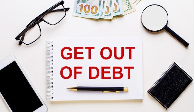 Sobre uma superfície clara, dólares, óculos, uma lupa, um telefone, uma caneta e um caderno com a inscrição saia da débita. conceito de negócios