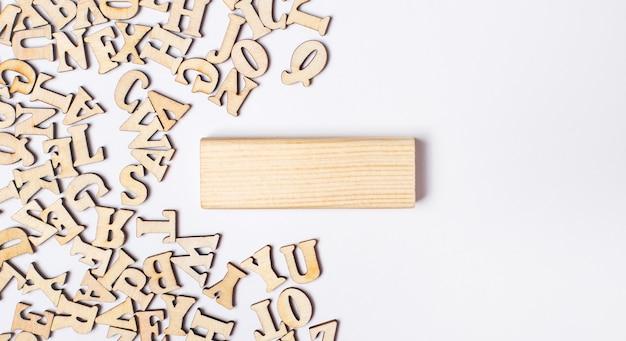Sobre uma superfície clara, letras de madeira e um bloco de madeira com local para inserir texto