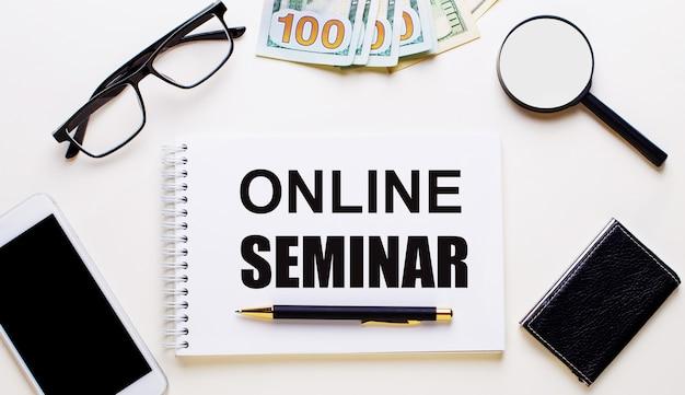 Sobre uma superfície clara, óculos, lupa, dinheiro, um telefone e um caderno com a inscrição seminário online