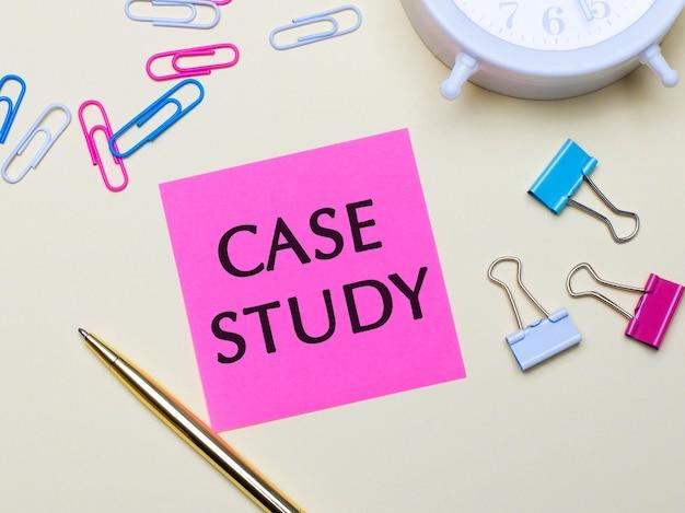 Sobre uma superfície clara, um despertador branco, clipes de papel rosa, azul e branco, uma caneta dourada e um adesivo rosa com o texto estudo de caso