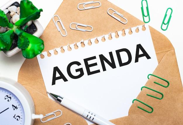 Sobre uma superfície clara, um envelope aberto, um despertador branco, uma planta verde, clipes de papel branco e verde, uma caneta branca e uma folha de papel com o texto agenda