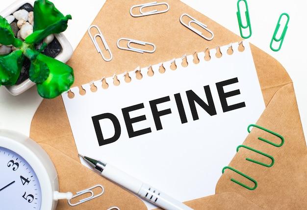 Sobre uma superfície clara, um envelope aberto, um despertador branco, uma planta verde, clipes de papel branco e verde, uma caneta branca e uma folha de papel com o texto define