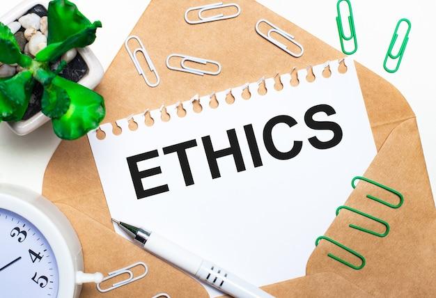 Sobre uma superfície clara, um envelope aberto, um despertador branco, uma planta verde, clipes de papel branco e verde, uma caneta branca e uma folha de papel com o texto ética