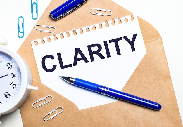 Sobre uma superfície clara, um envelope artesanal, um despertador, clipes, uma caneta azul e uma folha de papel com o texto clareza