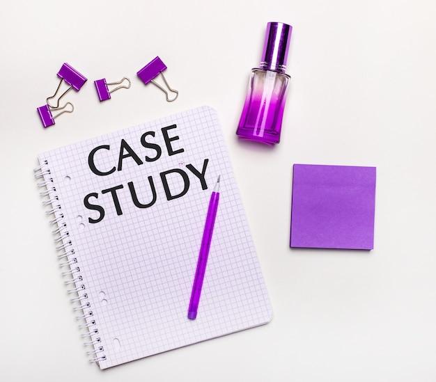 Sobre uma superfície clara um presente lilás, perfume, acessórios de negócios lilás e um caderno com uma inscrição lilás estudo de caso. postura plana.