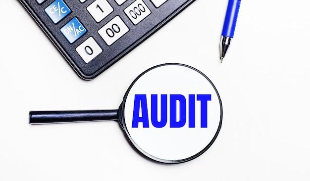 Sobre uma superfície clara, uma calculadora preta, uma caneta azul e uma lupa com texto dentro do audit